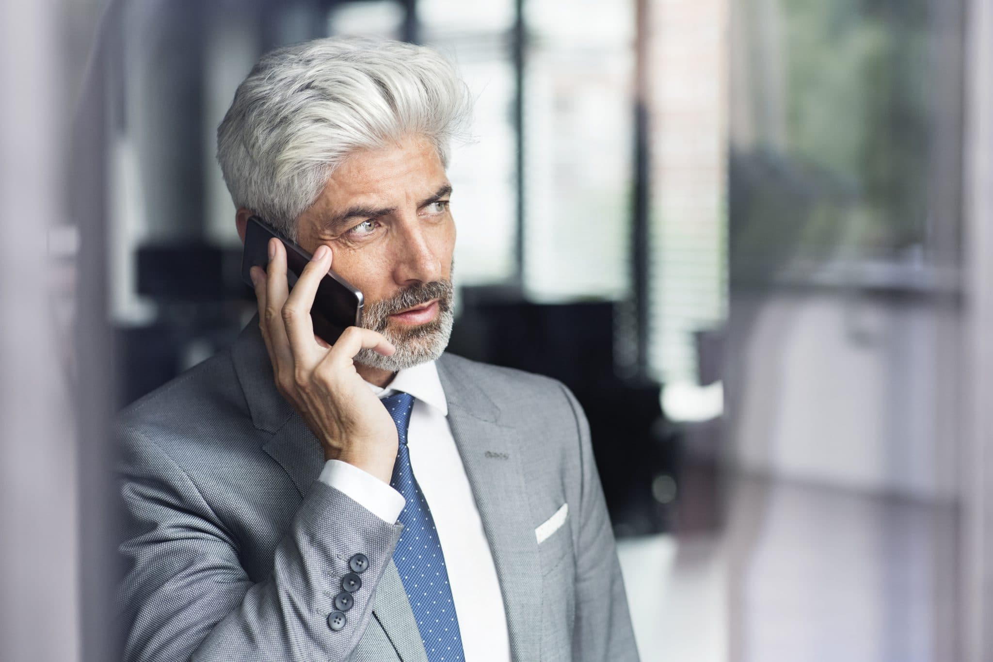 mature-businessman-with-smartphone-in-the-office-PSGYLJR
