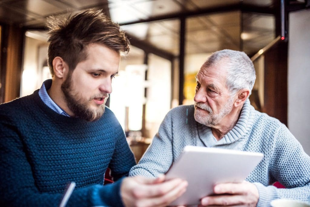 senior-father-and-young-son-with-tablet-in-a-cafe-PXL56G5