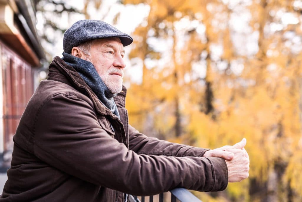 senior-man-resting-on-a-terrace-in-autumn-nature-PY6E7ZV